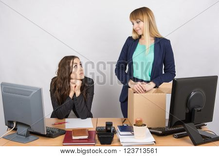 The Girl In The Office Is Facing The Box With Things And Looking At The Colleague Sitting Next