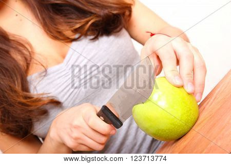 A young adult woman cutting fruits in the kitchen.