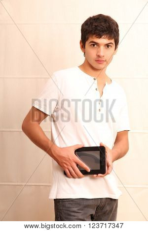 A young latin man with a Tablet PC face in focus ** Note: Soft Focus at 100%, best at smaller sizes