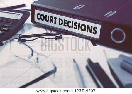 Ring Binder with inscription Court Decisions on Background of Working Table with Office Supplies, Glasses, Reports. Toned Illustration. Business Concept on Blurred Background.