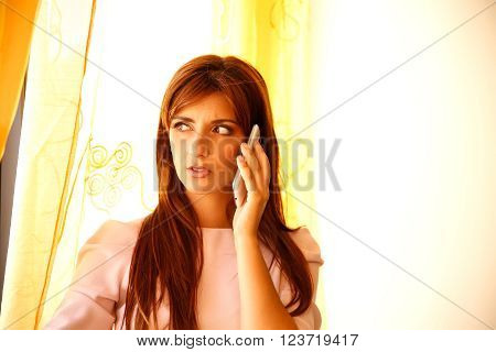 A beautiful woman waiting at the window while talking on the phone.