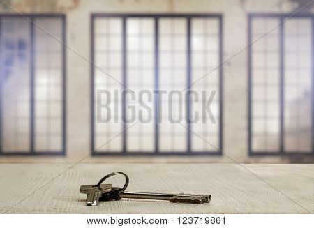 keys on white wooden table in old room with big windows