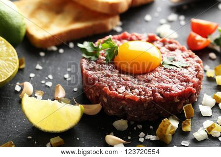 Beef Tartare With Egg Yolk On A Black Wooden Table