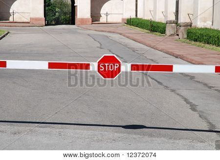 A red stop sign on a barrier across a paved road