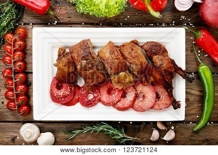 Roasted duck with apples. Roasted Peking duck. Baked duck legs and breasts at square plate. Duck and vegetables, tomatoes, peppers and garlic at wood, rustic wooden background.