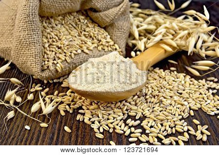 Flour oat in a wooden spoon, a bag of oat, stalks of oats on the background of wooden boards