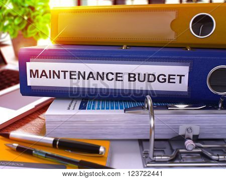 Blue Office Folder with Inscription Maintenance Budget on Office Desktop with Office Supplies and Modern Laptop. Maintenance Budget Business Concept on Blurred Background. 3D Render.