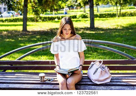 Young girl student sitting on a park bench, reading a paper book with a cup of coffee or a tea bag in a white jacket, a bright summer day outdoors, fashion lifestyle.