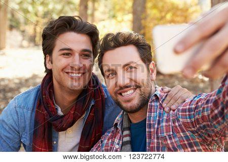 Gay Male Couple Taking Selfie On Walk In Woodland