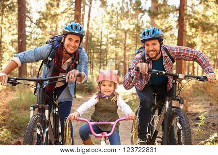 Gay Male Couple With Daughter Cycling Through Fall Woodland