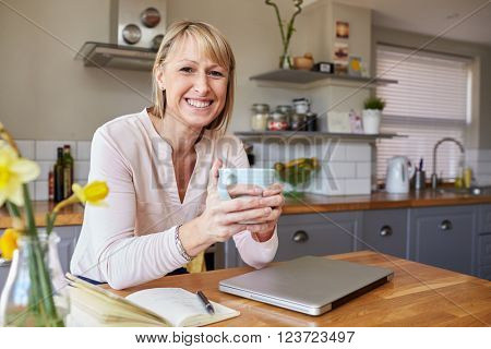Portrait Of Woman Working From Home On Laptop In Apartment