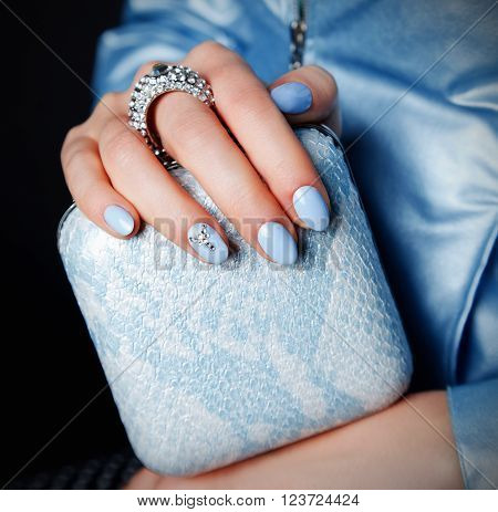 Close-up of a shiny party clutch with matching baby blue nails