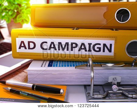 Yellow Office Folder with Inscription Ad Campaign on Office Desktop with Office Supplies and Modern Laptop. Ad Campaign Business Concept on Blurred Background. Ad Campaign - Toned Image. 3D Render.