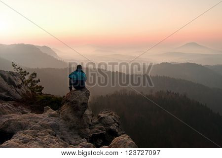 Tourist In Blue Wind Jacket Sit On Rocky View Point And Watching Into Misty Valley Bellow. Sunny Mis