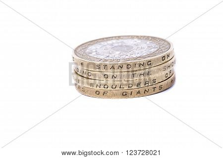 stack of british 2 pound coins showing motto standing on the shoulders of giants