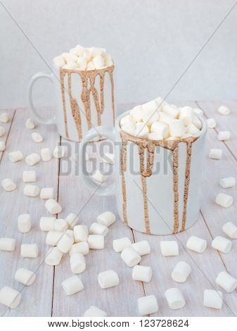 Hot chocolate with marshmallow topping in white mugs with drops