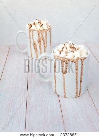 Hot cocoa with marshmallow and cocoa powder topping in white mugs with chocolate drops