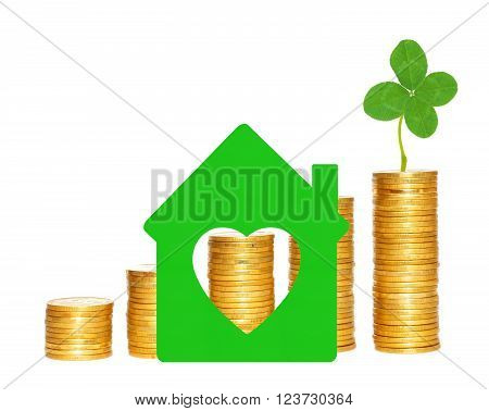 columns of gold coins clover and green house symbol over white background