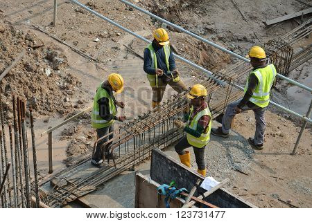 MALACCA, MALAYSIA -MARCH 25, 2016: Construction workers fabricating ground beam reinforcement bar at the construction site in Malacca, Malaysia.