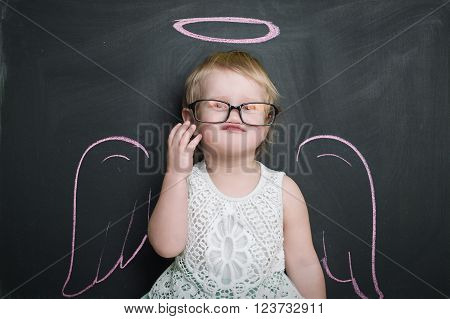 girl over chalkboard with funny angel wings and nimbus. Glasses
