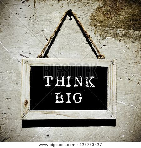 an aged chalkboard with the text think big hanging on a nail on a rustic wall, with a slight vignette added