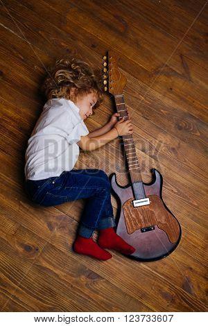 Little Boy Sleeping And Hugging Guitar On Wooden Floor