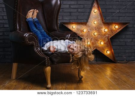 Little Boy Lying On Brown Leather Chair Near Iron Star On Brick Wall Background