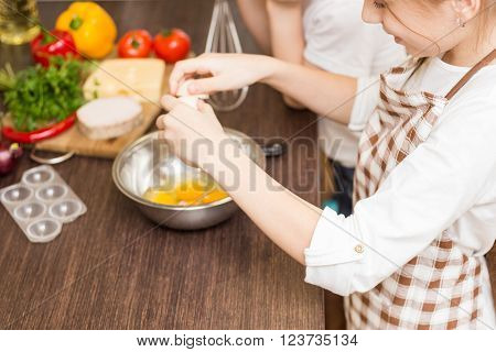 Teenage Girl Mixing Eggs In Bowl With Whisk