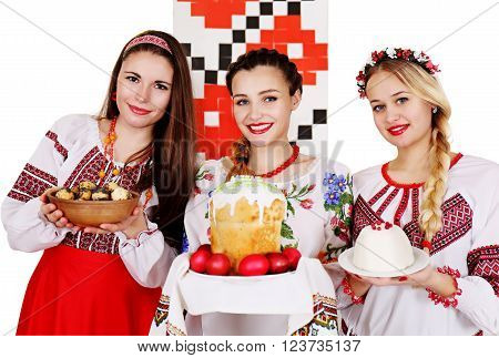 Three beautiful Ukrainian women in national costumes with Easter dishes