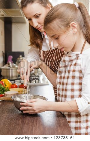 Mom And Daughter Mixing Eggs In Bowl With Whisk