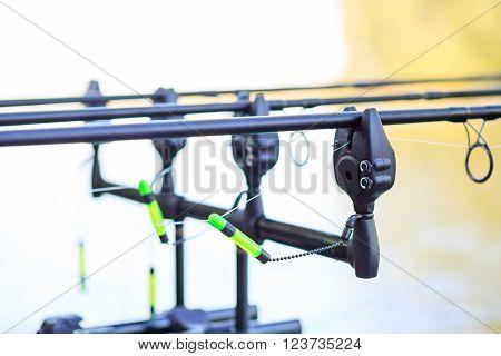 Carp fishing rods set up on holder with bite alarms and illuminated indicators . Professional fishing equipment