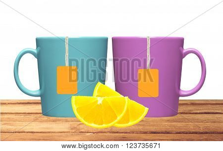 Two cups lemon and tea bags with orange label on table isolated on white background