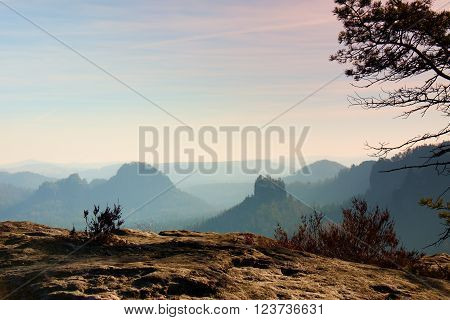 Amazing daybreak in Saxony Switzerland park. Sandstone peaks increased from foggy background