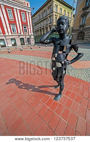TIMISOARA ROMANIA - MARCH 20 2016: View of the Liberty-Square in Timisoara Romania with a modernist metal statue in the foreground.
