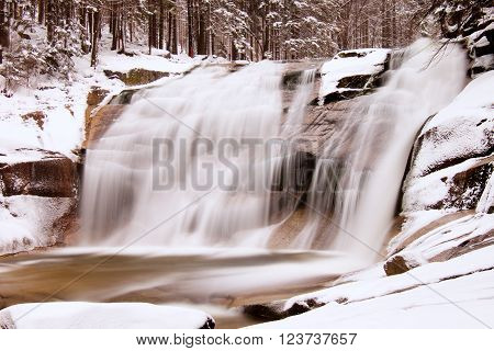 Winter view over snowy boulders to cascade of waterfall. Wavy water level. Stream in deep freeze.