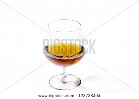 A glass of excellent brandy on a white background