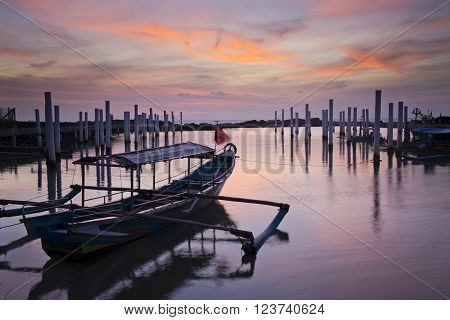 a tied fishing boat and the sunset