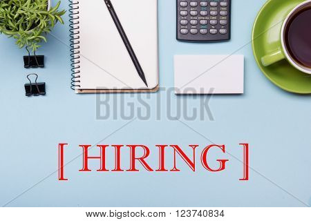 Headhunting Hiring HR Human Resources Position Concept. Office supplies on desk table top view. Notepad, magnifying glass coffee cup and flower