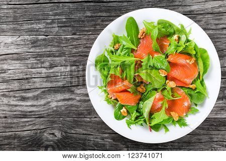 Red fish healty salad with mixed lettuce leaves on a white dish on a old rustic table easy recipe top view