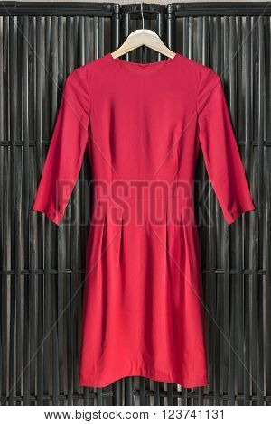 Red dress on clothes rack hanging on black bamboo screen