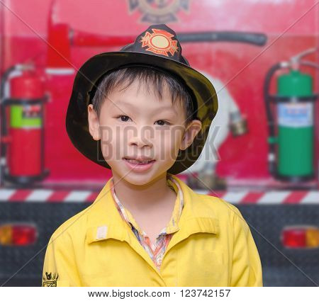 Little Asian boy in fire fighter costume