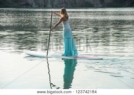 SUP the girl in a white dress with a paddle board floats on water