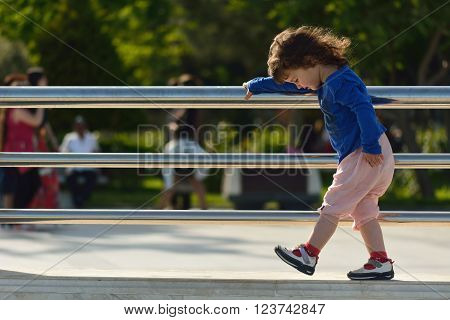 Young girl walking on wall holding metal railings. A small child taking careful steps on a wall, holding a railing and looking at her feet