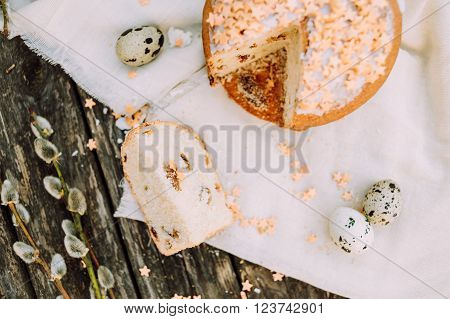 Slice of Easter cake with quail eggs on wooden rustic table, top view