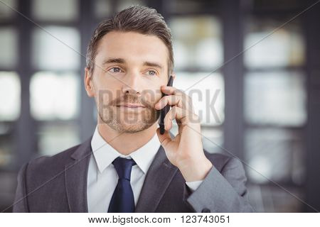 Close-up of handsome businessman talking on cellphone in office
