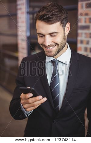 Close-up of happy businessman using cellphone in office
