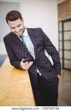 Happy businessman looking in cellphone while leaning on counter at office