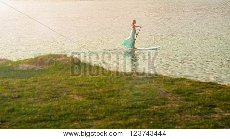 athletic girl stand up paddleboard. SUP the girl in a white dress with a paddle board floats on water