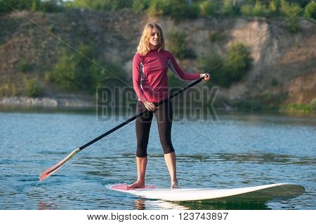 confident woman standing with a paddle on the surfboard