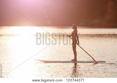 silhouette of young girl paddle boarding at sunset